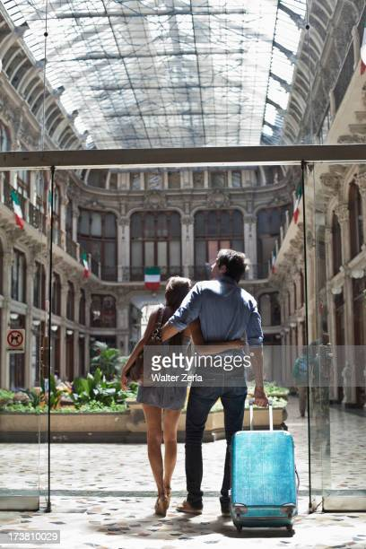 Caucasian couple pulling luggage into ornate building
