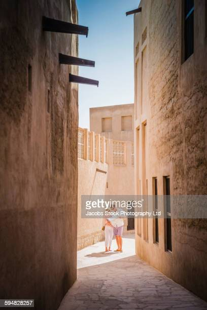 Caucasian couple reading map in alley