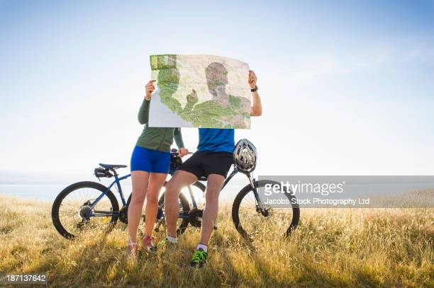 Caucasian couple reading map in rural landscape