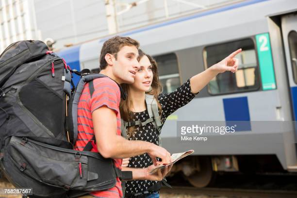 Caucasian couple reading map near train and pointing