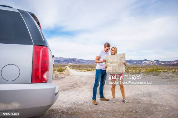 Caucasian couple reading map on road trip