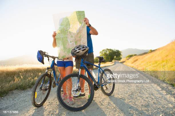 Caucasian couple reading map on rural road