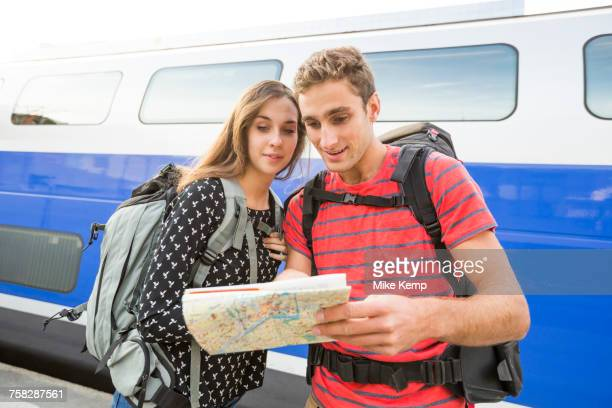 Caucasian couple reading math near train