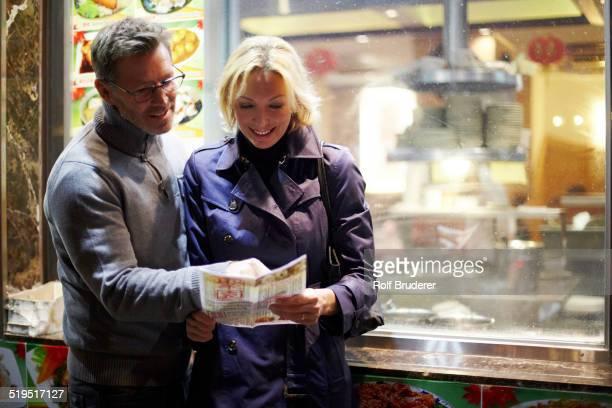 Caucasian couple reading menu at food cart, New York City, New York, United States