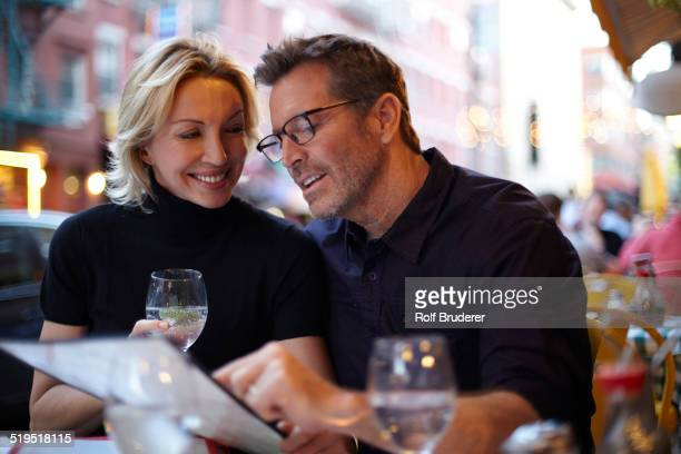 Caucasian couple reading menu at urban cafe, New York City, New York, United States