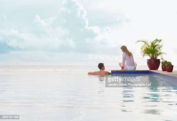 Caucasian couple relaxing at swimming pool