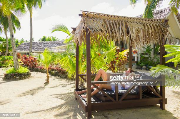 Caucasian couple relaxing in cabana on tropical beach