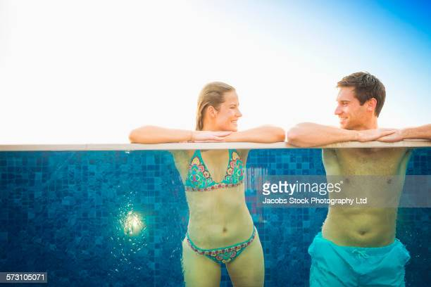 Caucasian couple relaxing in swimming pool