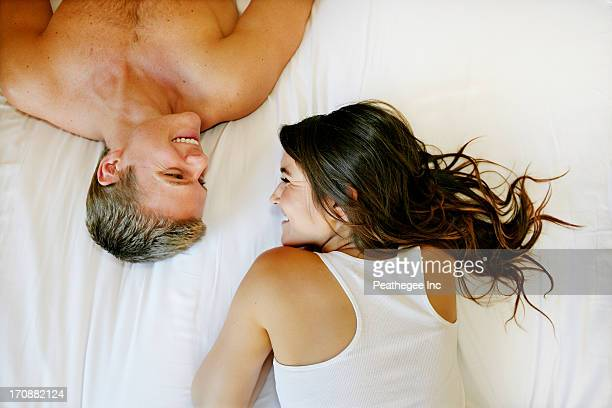 Caucasian couple relaxing on bed