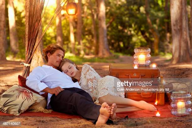 Caucasian couple relaxing on blanket in forest