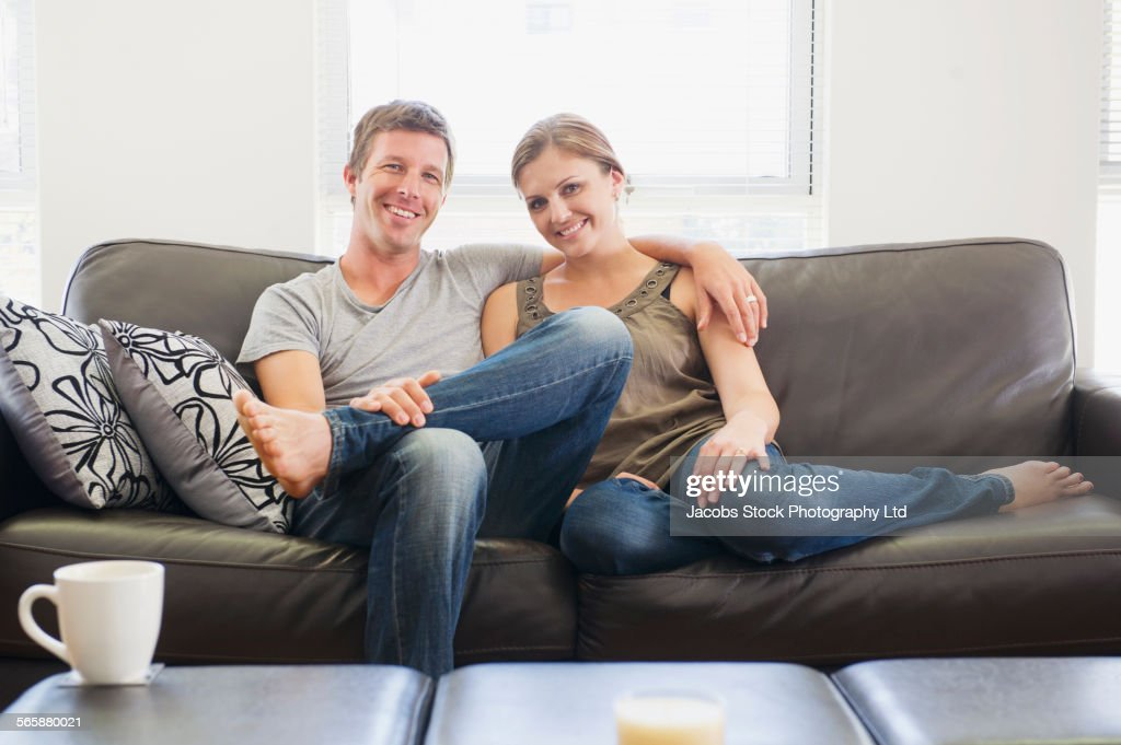 Caucasian couple relaxing on living room sofa