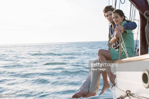 Caucasian couple relaxing on sailboat