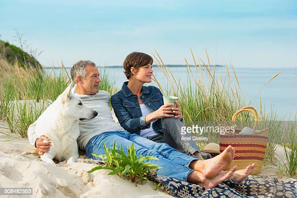 Caucasian couple relaxing with dog on beach
