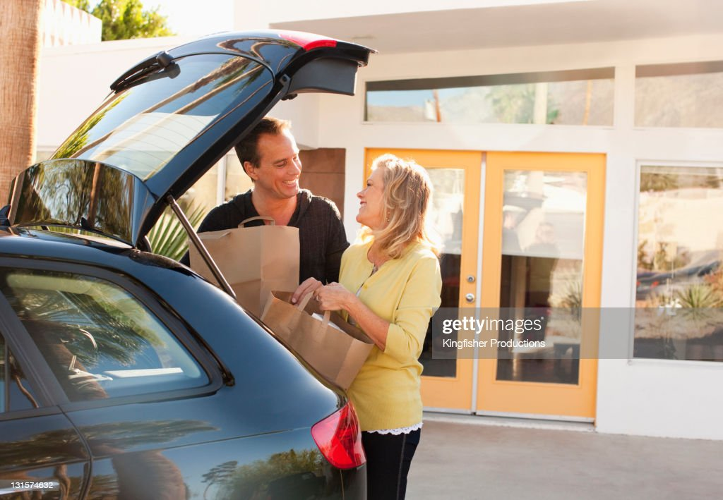 Caucasian couple removing groceries from car