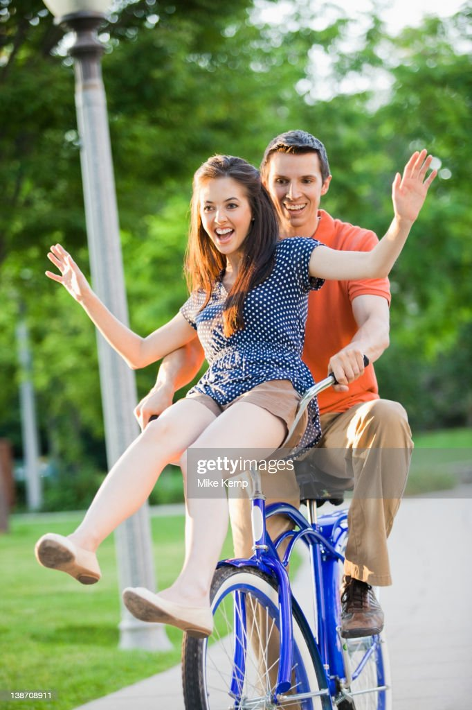 Caucasian couple riding bicycle together : Stock Photo