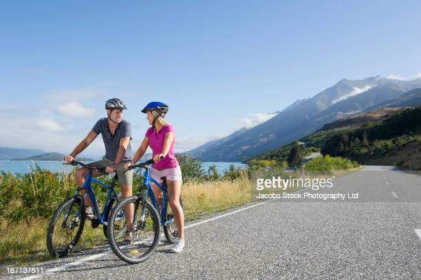 Caucasian couple riding bicycles on rural road