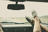 Caucasian couple riding in car with feet on dashboard
