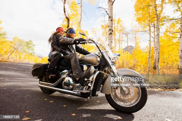 Caucasian couple riding motorcycle