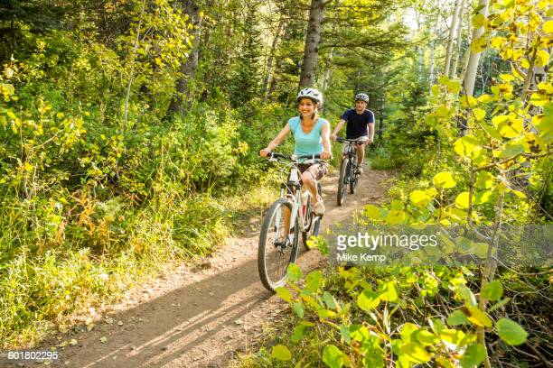 Caucasian couple riding mountain bikes