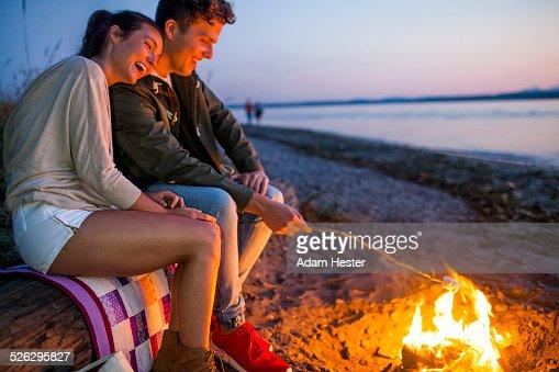 Caucasian couple roasting marshmallows on fire at beach