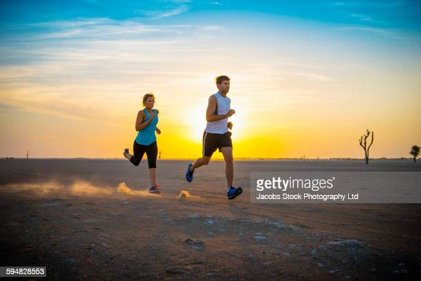 Caucasian couple running in desert