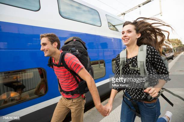Caucasian couple running near train