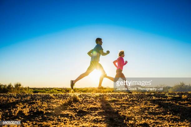Caucasian couple running on remote road