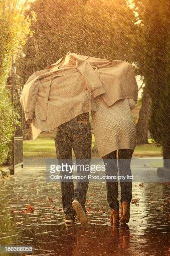 Caucasian couple running under coat in rain