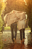Caucasian couple running under coat in rain