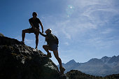Caucasian couple scaling boulder