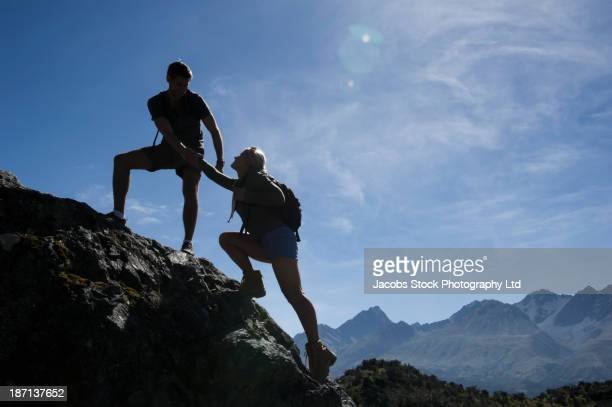 Caucasian couple scaling boulder