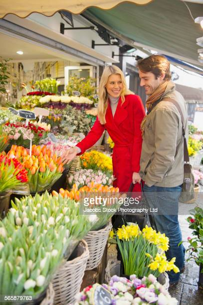 Caucasian couple shopping for flowers in market