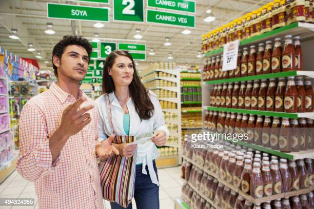 Caucasian couple shopping in grocery store