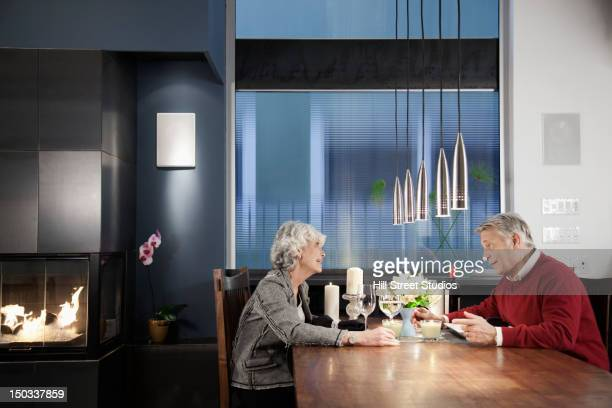 Caucasian couple sitting at elegant dining room table