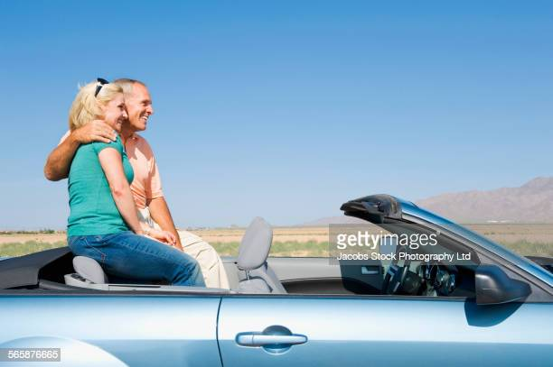 Caucasian couple sitting in convertible in desert