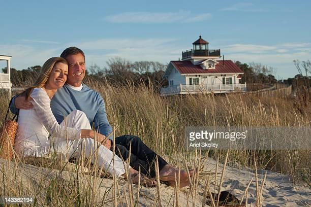 Caucasian couple sitting on beach