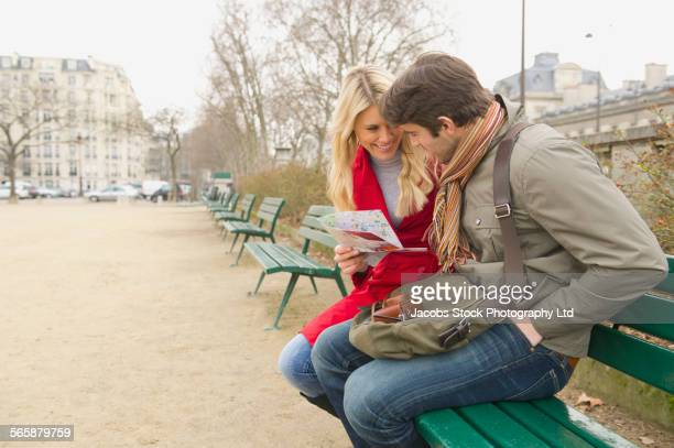 Caucasian couple sitting on bench in urban park