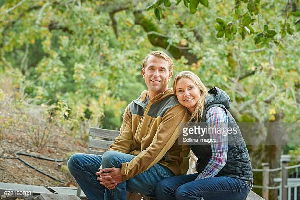 Caucasian couple sitting on bench outdoors