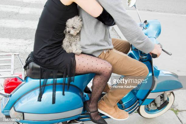 Caucasian couple sitting on scooter