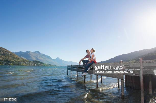 Caucasian couple sitting on wooden dock