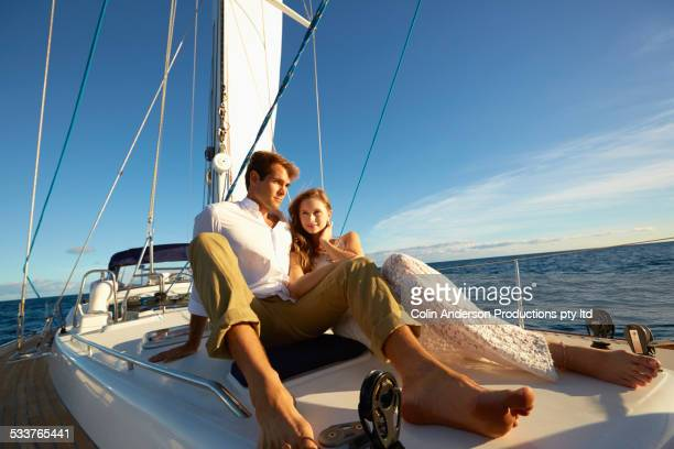 Caucasian couple sitting on yacht deck