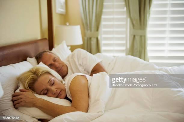 Caucasian couple sleeping in bed