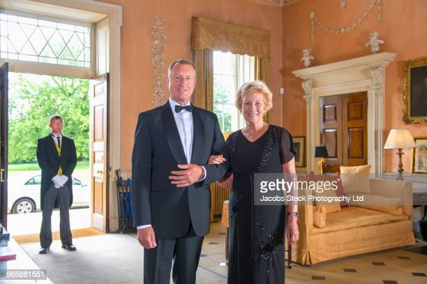 Caucasian couple smiling in mansion formal parlor