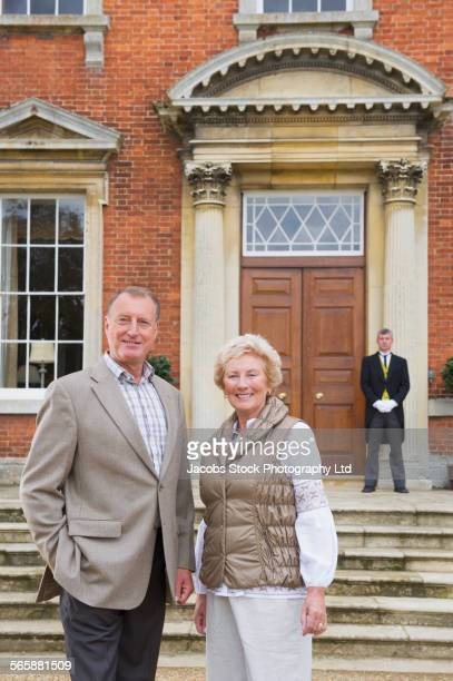 Caucasian couple smiling outside mansion with butler