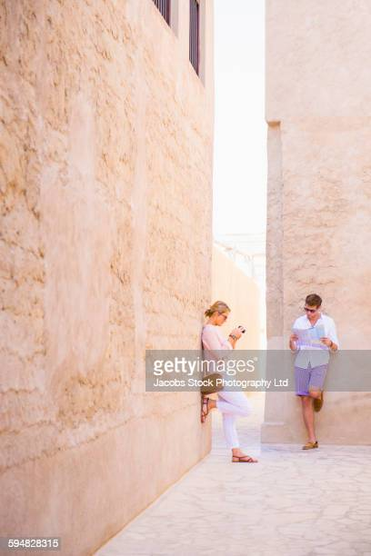 Caucasian couple standing under stone walls