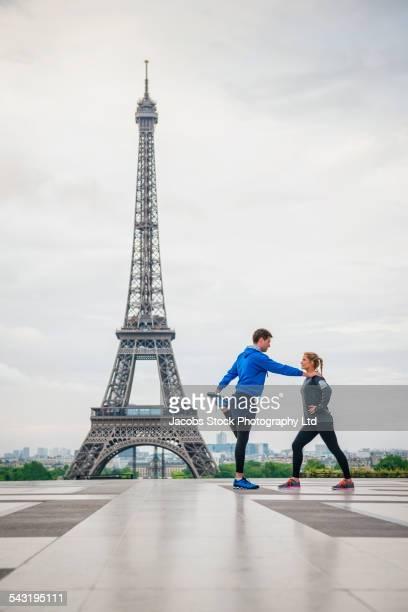 Caucasian couple stretching near Eiffel Tower, Paris, France