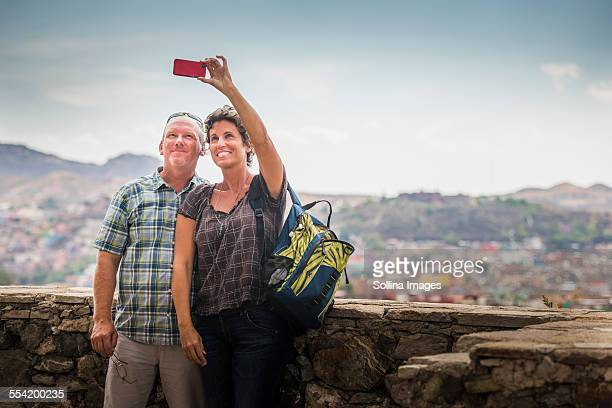 Caucasian couple taking cell phone photograph together on rooftop