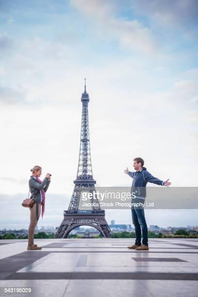 Caucasian couple taking photograph near Eiffel Tower, Paris, France