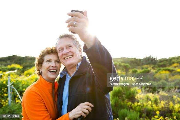 Caucasian couple taking picture outdoors