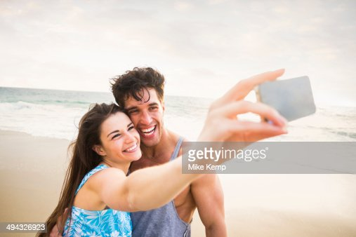 Caucasian couple taking pictures on beach